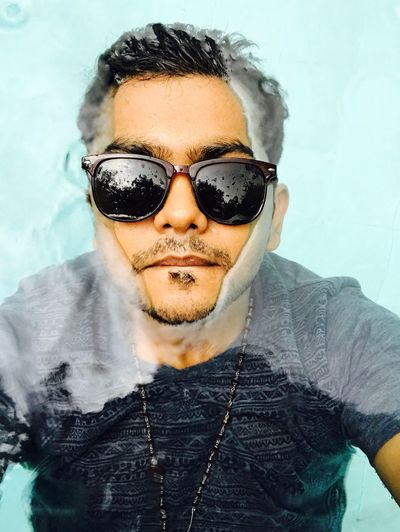 High Angle Portrait Of Young Man Wearing Sunglasses Swimming In Pool