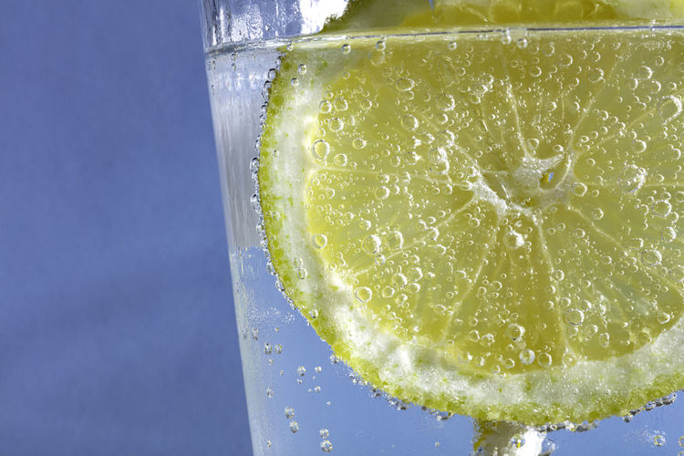 Close-up of lemon drink in glass against blue background
