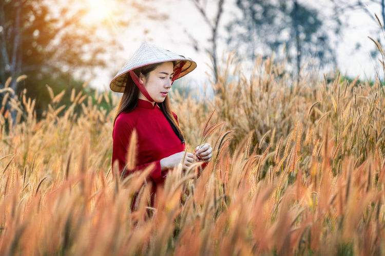 Asian woman wearing Vietnam culture traditional in african fountain flower field. Plant Hat Land Field One Person Grass Clothing Nature Selective Focus Leisure Activity Casual Clothing Three Quarter Length Women Day Hair Standing Lifestyles Side View Child Hairstyle Outdoors
