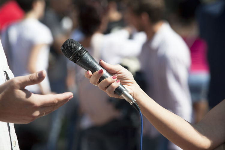 Media interview. Broadcast journalism. Journalist Mic PR Press Holding Human Hand Information Journalism Mass Media Media Media Event Media Interview Microphone News News Conference Outdoors People Press Interview Public Relations Question Report Reportage Reporter