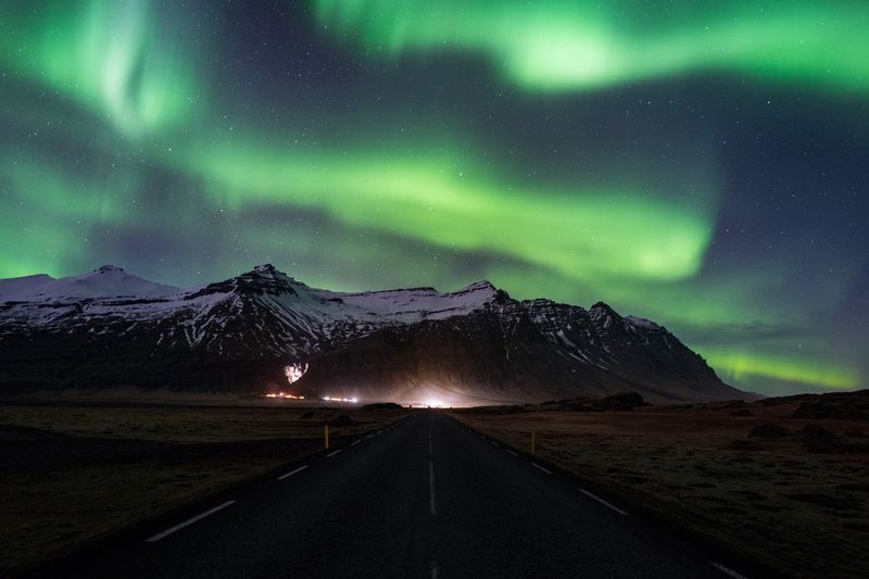 Road Leading Towards Mountain During Aurora Borealis
