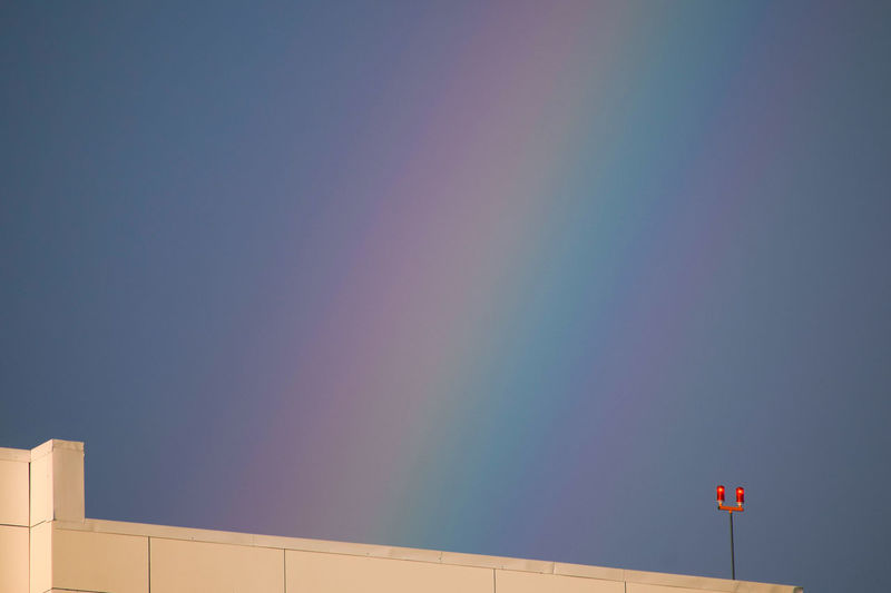 Close-up of rainbow over building against sky