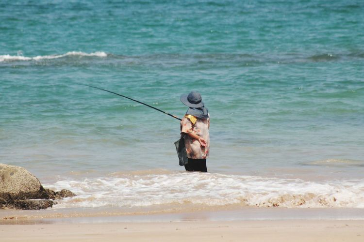 Sea Fishing Water Wave Rear View Beach Weekend Activities Standing Children Only Outdoors One Person Full Length Day Fishing Net Working People