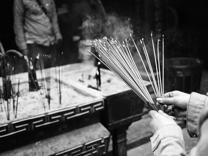 Cropped Hand Of Woman Holding Incense Sticks