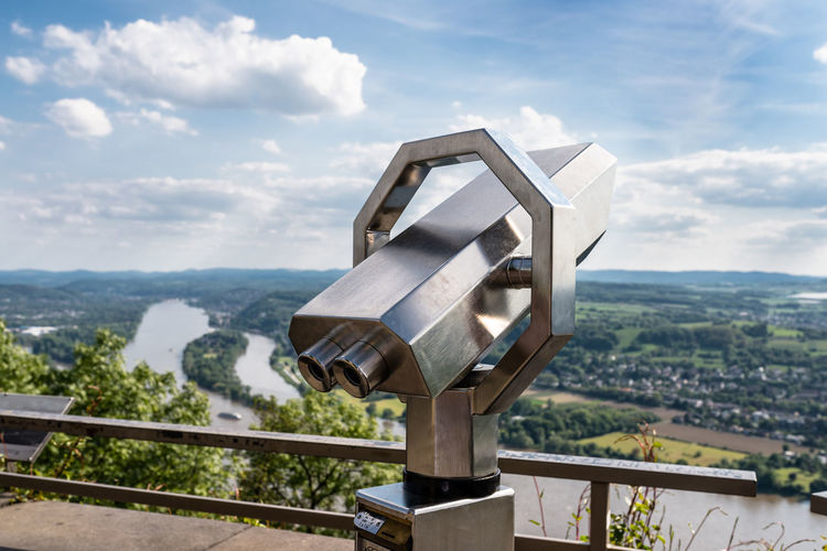 A paid binocular telescope, set on a high vantage point with a view of the city.