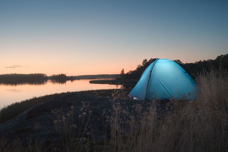 Glowing tent on the shores of a picturesque lake during the white nights