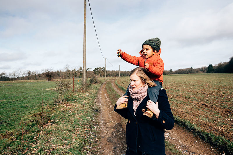 Young mother and son having fun together outdoor in countryside - focus on african baby face