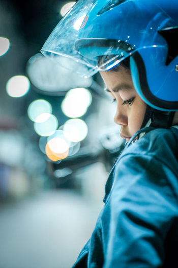Boy wearing a helmet with worried looking face at the street. Children safety awareness image. Adult Blue Blue Boy Boys Focus On Foreground Headshot Helmet Illuminated Indoors  Looking Males  Men Night Occupation One Person Portrait Protection Real People Safety Selective Focus Side View Technology Young Adult