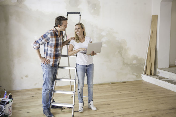 Man and woman looking at a computer whilst renovating a yoga studio Casual Clothing Computer Day Full Length Ladder Leisure Activity Lifestyles Man And Woman Man And Woman Smiling Renovations Sky Smoke - Physical Structure Teamwork Young Adults