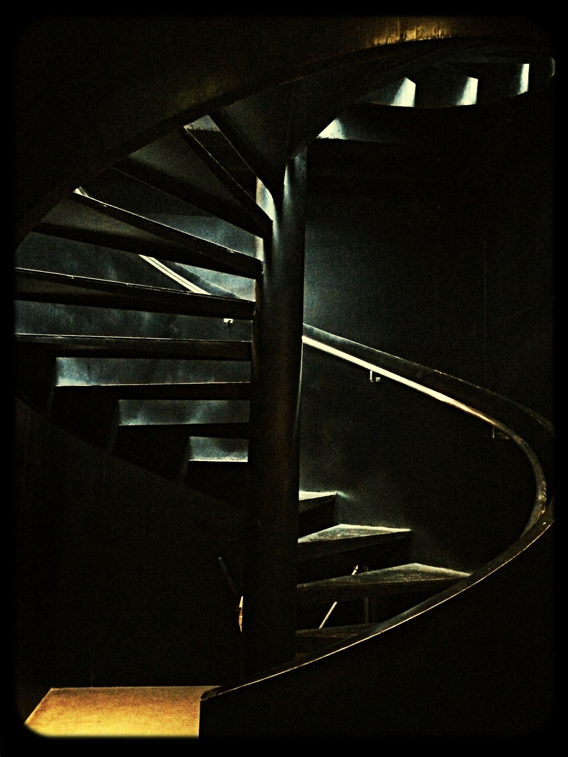 indoors, railing, architecture, steps and staircases, built structure, staircase, steps, illuminated, low angle view, metal, transfer print, auto post production filter, absence, no people, empty, high angle view, diminishing perspective, connection, transportation, technology