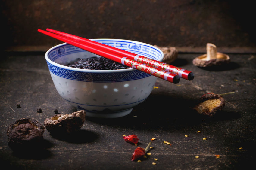 Porcelain bowl of uncooked black rice, served with dry shiitake mushrooms and red chopsticks over dark table. Asian Food Asian Style Black Rice Bowl Chili Peppers Chinese Food Chopsticks Dark Photography Food Raw Food Red Rice Shiitake Mushrooms Uncooked