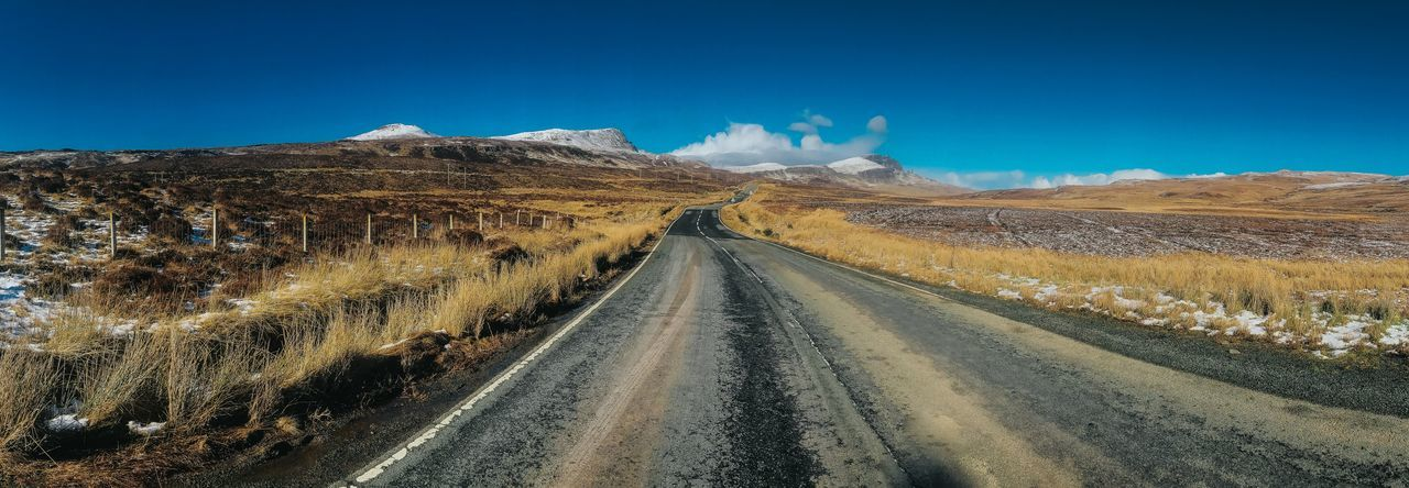 Panoramic view of road leading towards mountains against blue sky