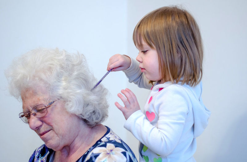 Playful woman with granddaughter at home