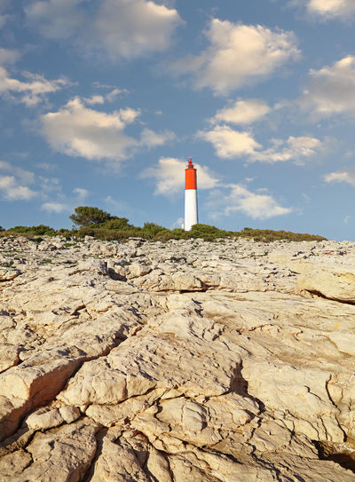 Lighthouse on rock by building against sky
