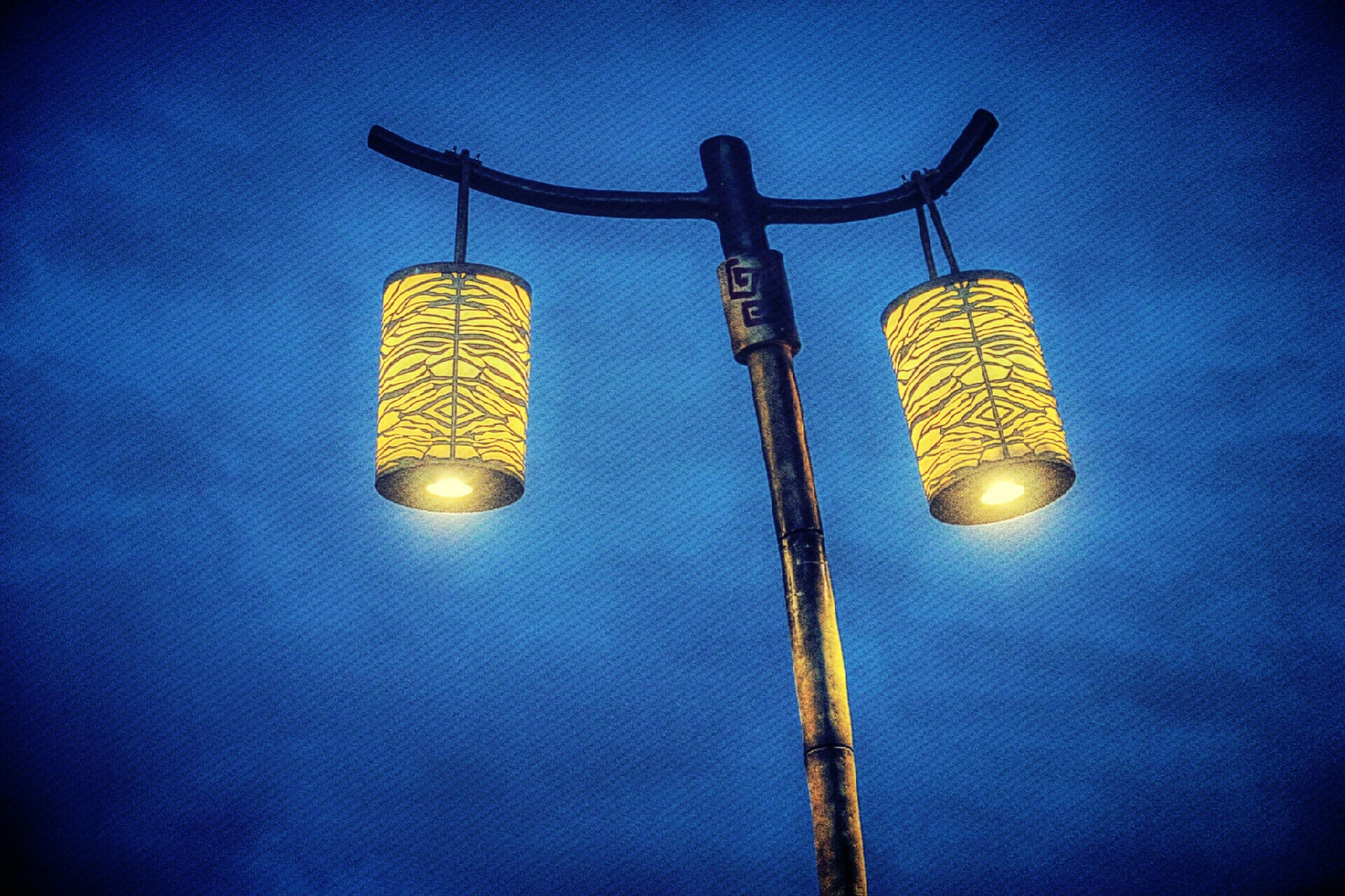 low angle view, illuminated, lighting equipment, electricity, hanging, electric light, street light, light bulb, glowing, night, sky, blue, light - natural phenomenon, decoration, electric lamp, close-up, no people, technology, lantern, metal