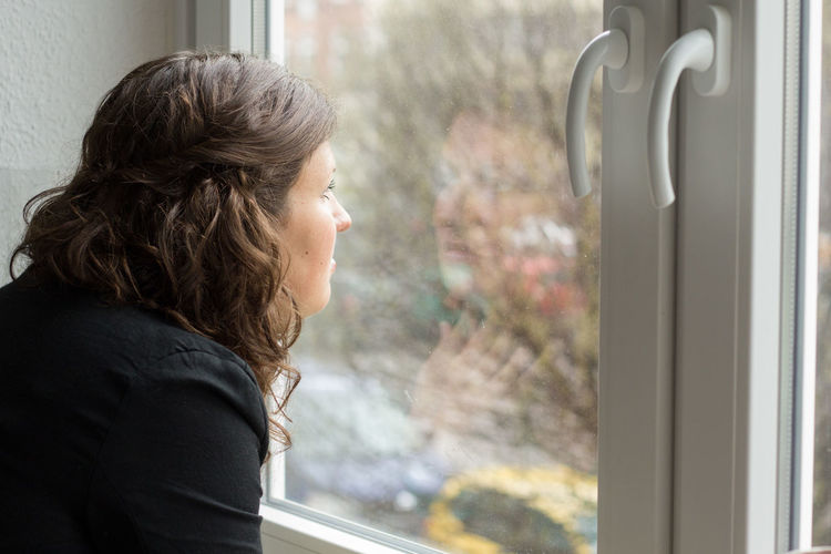CLOSE-UP OF WOMAN Peering Out Of Window