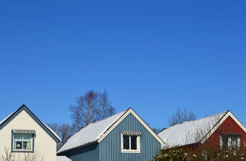 Houses against clear blue sky during winter