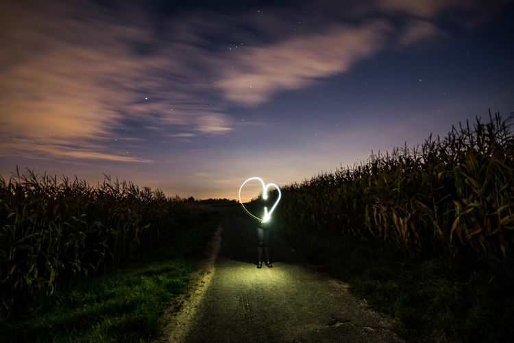Person with heart shape light painting standing on road against sky