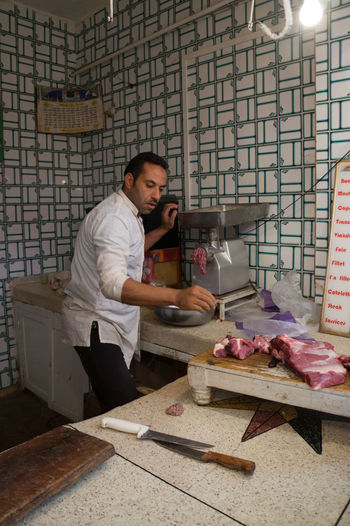 Butcher Weighing Meat On Scale At Store
