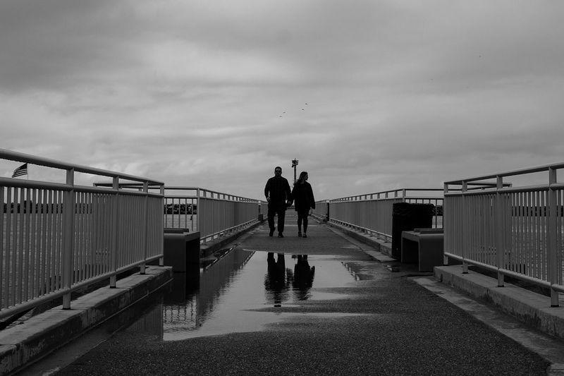 People walking on footbridge against sky