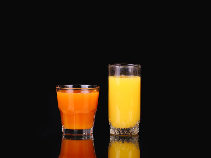 Glass of juice against black background