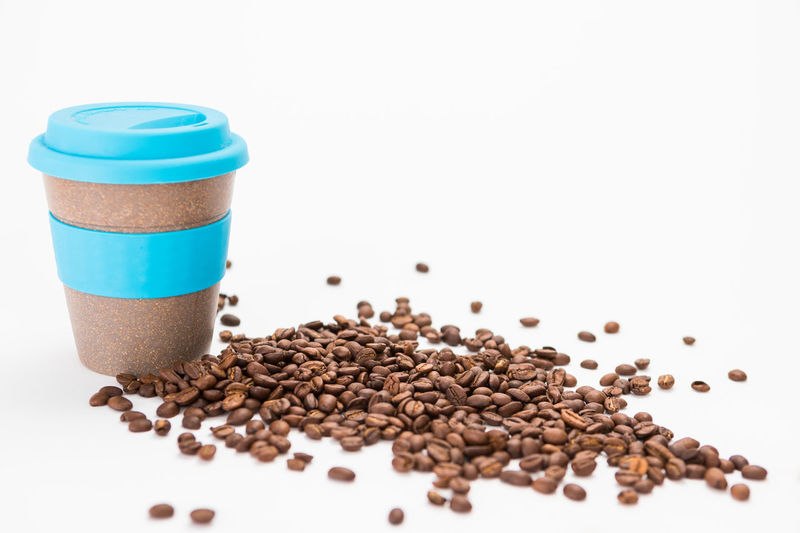 Coffee cup to Go with Coffee Beans on the white Background Studio Shot Food And Drink White Background Still Life Indoors  Coffee Coffee - Drink Roasted Coffee Bean Freshness Large Group Of Objects No People Brown Food Close-up Copy Space Table Drink Coffee Cup Refreshment Cup Caffeine