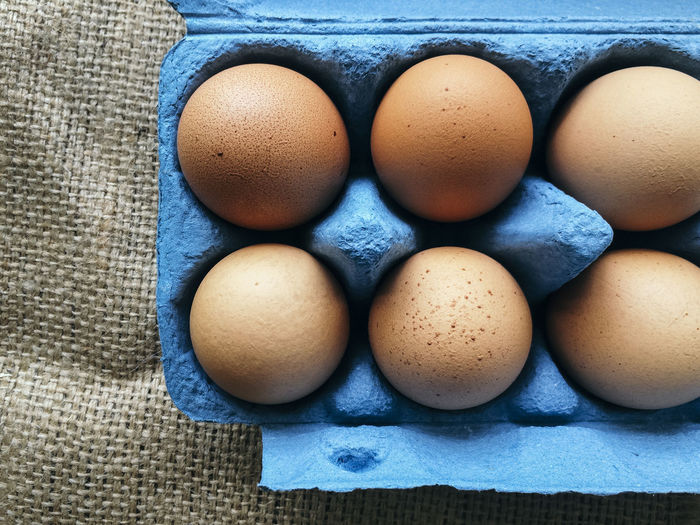 Directly Above View Of Brown Eggs In Blue Carton On Jute