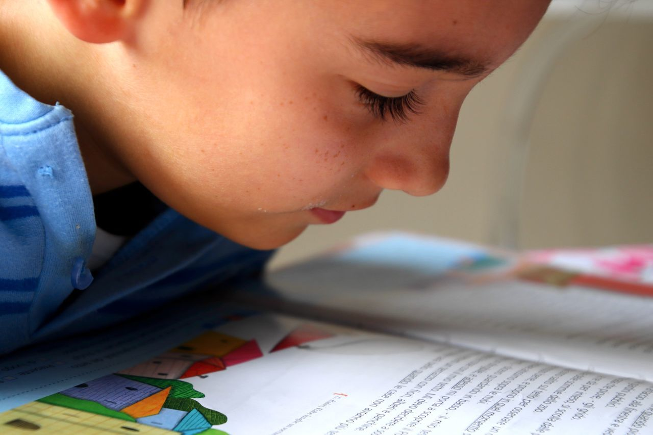 Close-Up Of Boy Studying At Home