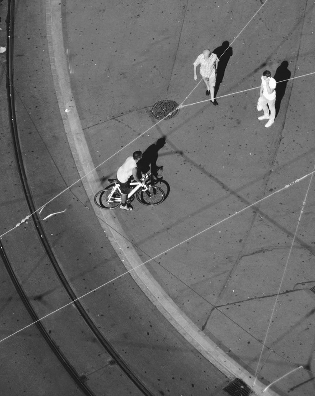 HIGH ANGLE VIEW OF PEOPLE RIDING BICYCLES ON FOOTPATH