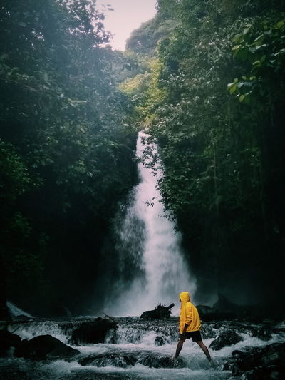 Side View Of Young Man Wading By Waterfall In Forest