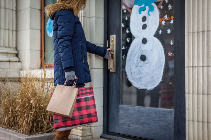 Christmas Holidays Shopping Small Business Adult Blond Hair Building Exterior City Consumerism Customer  Day Door Lifestyles One Person One Woman Only Opening Outdoors People Shop Shopping Bag Store Warm Clothing Women Young Adult Young Women