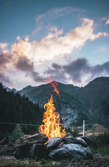 Ice Cold Fire, Switzerland - DSLR Mountain Burning Sky Cloud - Sky Flame Nature Heat - Temperature Fire Scenics - Nature Fire - Natural Phenomenon Beauty In Nature Tree Mountain Range Environment Land Plant Non-urban Scene Rock Bonfire Tranquil Scene No People Outdoors Wood Campfire Mountain Peak