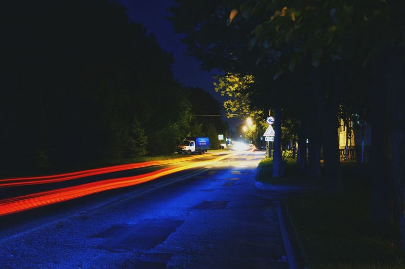 Light trails on road amidst trees in city at night