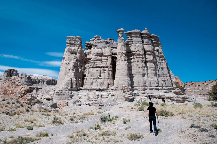 Rear view full length of woman against rock formation at plaza blanca in abiquiu