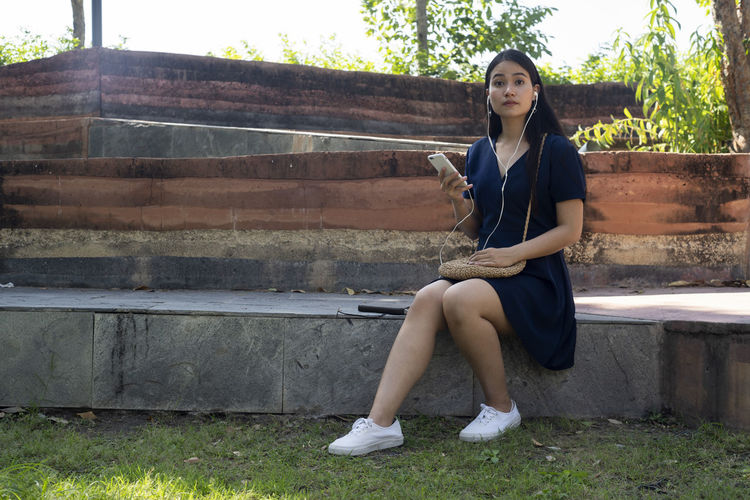 Portrait of a smiling young woman sitting on bench