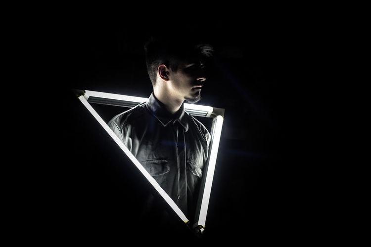 Man standing amidst illuminated lights black background
