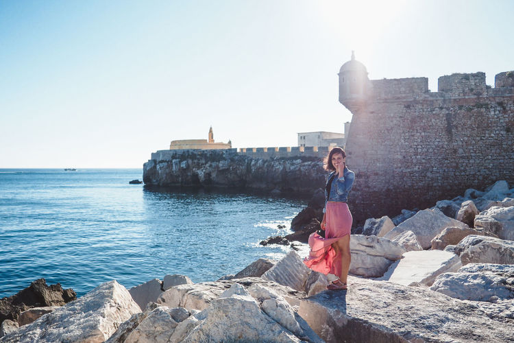 Full Length Of Woman Standing On Rock By Sea Against Sky During Sunny Day