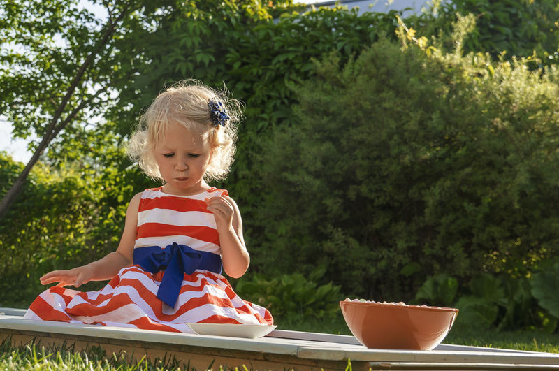 Pretty curly little girl seating in garden and eating marshmallows from the plate.