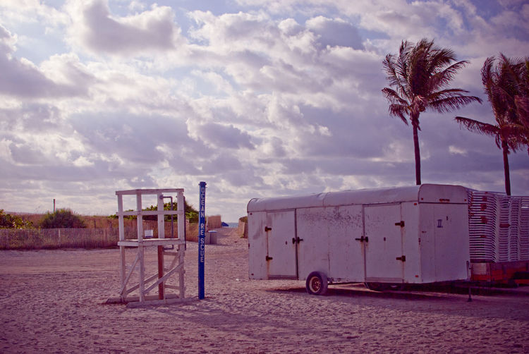 Trailers at beach against cloudy sky