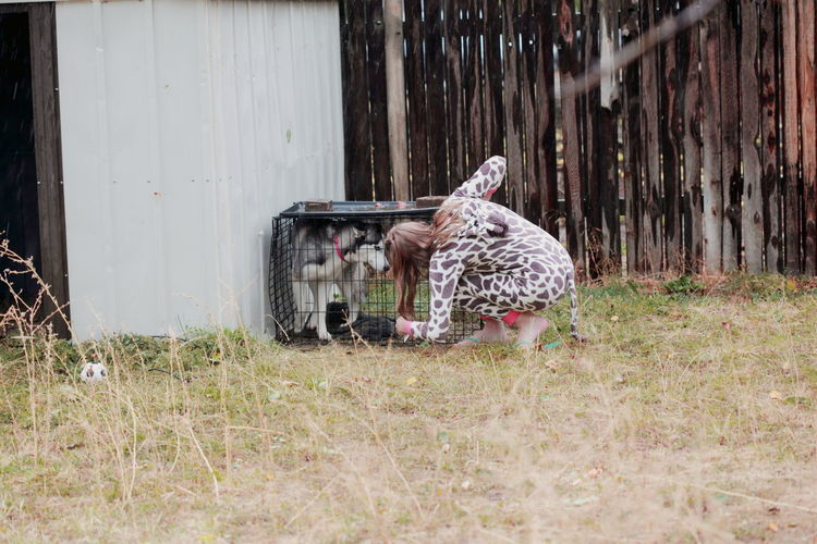 Rear View Full Length Of Woman Looking At Husky In Cage On Field