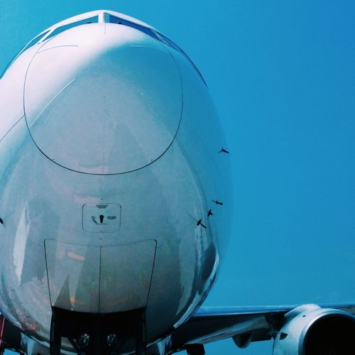 Close-up of an airplane against blue sky