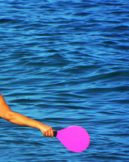 Cropped image of person holding table tennis racket against sea