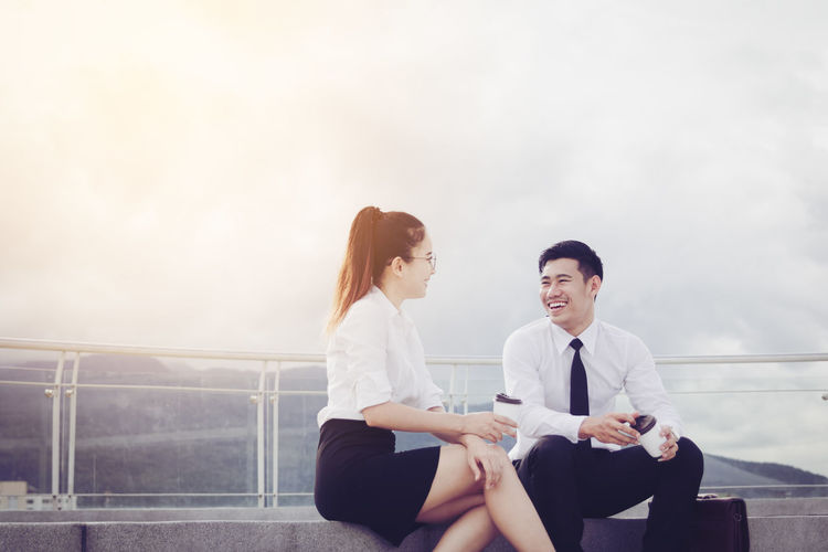 Cheerful Business Coworkers Talking While Sitting Against Cloudy Sky