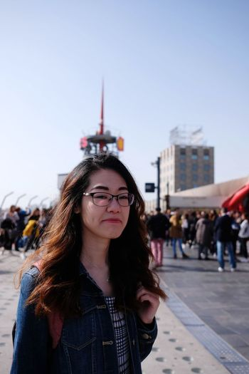Portrait of beautiful young woman in city against sky