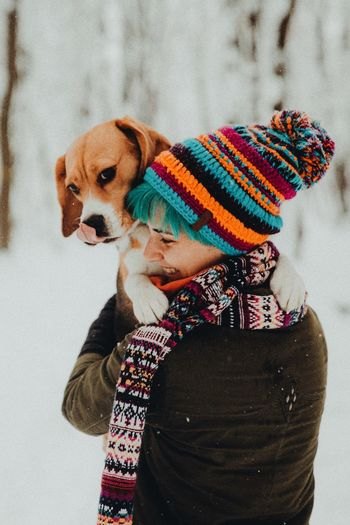 Rear view of young woman carrying beagle while standing in forest during winter