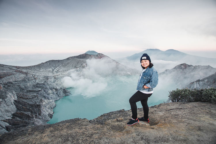 Portrait of woman standing against hot spring amidst mountains