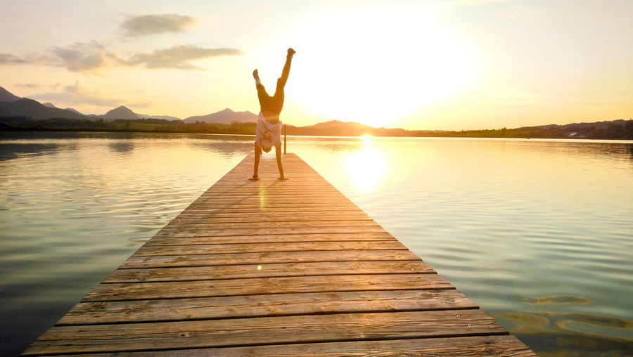 Woman doing handstand on pier over lake during sunset