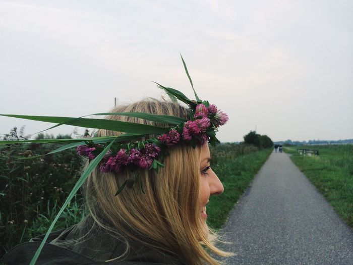 Young woman wearing tiara standing on road amidst grassy field against sky