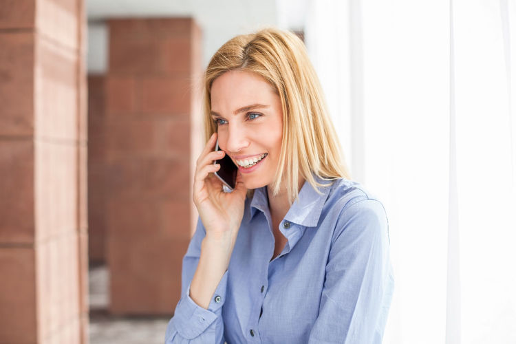 Confident businesswoman talking on smart phone in office lobby