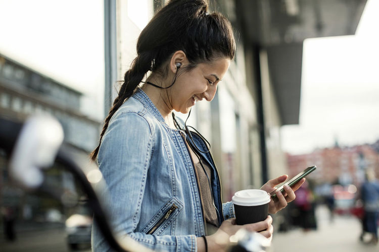 Side view of young woman using mobile phone